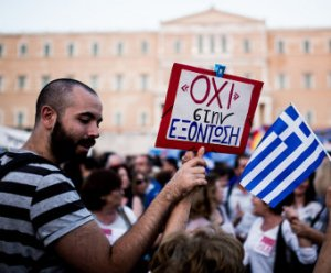 "A protestor outside the Greek parliament building on 29 June 2015, holding a sign reading ""ΟΧΙ"" στην  ΕΞΌΝΤΩΣΗ (""no to annihilation""). Photo by janwellman (CC BY-SA 3.0)."
