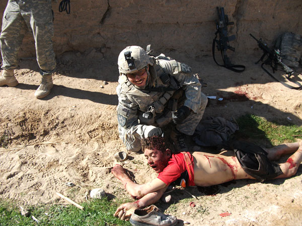 US Soldier next to corpse of unarmed civilian.