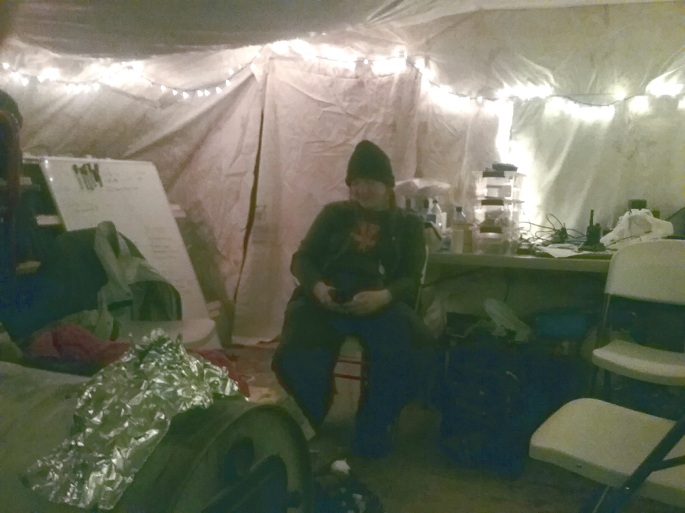 A Water Protector on the tech team takes a break in the warm tent.